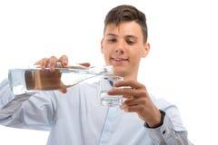 Agua de colada del camarero del adolescente de la botella de cristal en un vidrio aislado Imagen de archivo libre de regalías