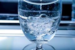 Agua de colada en un vidrio Imagen de archivo libre de regalías