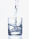 Agua de colada en un vidrio Imagenes de archivo