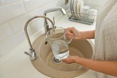 Agua de colada de la mujer en el jarro de cristal en cocina imágenes de archivo libres de regalías