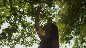 Agua de colada de la mujer preciosa del ajuste sobre cuerpo en la puesta del sol almacen de metraje de vídeo