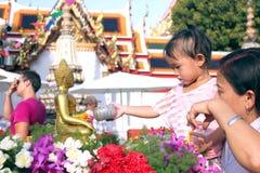 Agua de colada sobre Buda, mujeres que vierten el agua sobre el statu de Buda Fotografía de archivo libre de regalías