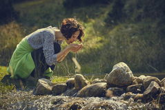 Agua de consumición de la corriente de la montaña de la mujer Fotografía de archivo