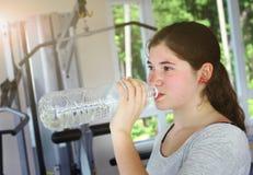 Agua de la bebida de la muchacha del adolescente de la botella Fotos de archivo libres de regalías