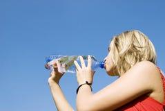 Agua de la bebida de la mujer de la botella Fotos de archivo