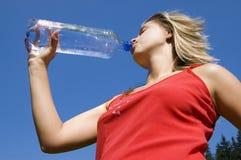 Agua de la bebida de la mujer de la botella Imágenes de archivo libres de regalías