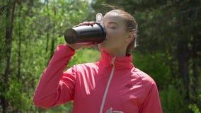Agua de la bebida de la mujer después del deporte almacen de metraje de vídeo