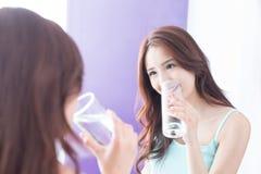 agua de la bebida de la mujer joven imagenes de archivo