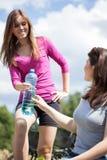 Agua de la bebida de las muchachas en viaje de la bicicleta imágenes de archivo libres de regalías