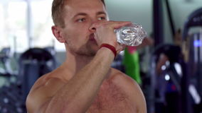Agua de la bebida del hombre en el gimnasio almacen de metraje de vídeo
