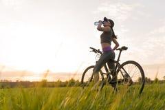 Agua de la bebida durante entrenamientos deportes mujer en puesta del sol de la bici foto de archivo libre de regalías