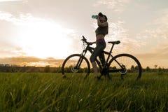 Agua de la bebida durante entrenamientos deportes mujer en puesta del sol de la bici imagen de archivo