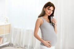 Agua de la bebida Agua potable de la mujer embarazada del vidrio fotos de archivo