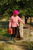 Agua de la cucharada de la gente del pozo de agua Foto de archivo