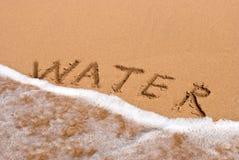 Agua de la inscripción en la arena en la playa fotos de archivo