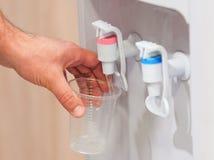 Agua de la porción de la mano de un refrigerador de agua Foto de archivo
