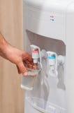 Agua de la porción de la mano de un refrigerador de agua Imágenes de archivo libres de regalías