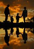 Agua de la puesta del sol de la familia de cuatro miembros Imágenes de archivo libres de regalías