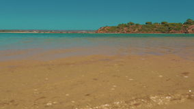 Agua de la turquesa del tiro de la orilla de la playa del ángulo bajo en el Algarve, Portugal almacen de metraje de vídeo