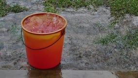 Agua de lluvia que cae del tejado en el cubo rojo almacen de metraje de vídeo