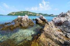 Agua de mar azul clara con la montaña de piedra y grande. Fotos de archivo libres de regalías