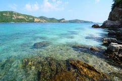 Agua de mar azul clara con la montaña de piedra y grande. Foto de archivo
