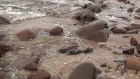 Agua de mar que se lava sobre rocas en una playa arenosa en Escocia almacen de metraje de vídeo