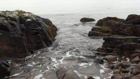 Agua de mar que se lava sobre rocas en una playa arenosa en Escocia almacen de video