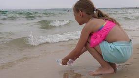 Agua de mar de relleno del adolescente de la muchacha a embotellar mientras que juego en la playa del verano almacen de video