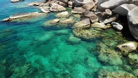 Agua de mar tranquilo cerca de piedras Agua de mar azul pacífica y cantos rodados grises en el lugar perfecto para bucear en Koh  almacen de metraje de vídeo