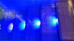Agua de ondulación colorida de la piscina interior metrajes