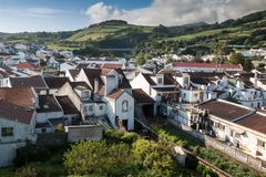 Agua de Pau, Sao Miguel, Azores Islands. Aerial view on the city, with its white houses and a church built in traditional portuguese style. Mountains and a royalty free stock image