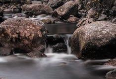 Agua de río que atraviesa rocas Imágenes de archivo libres de regalías