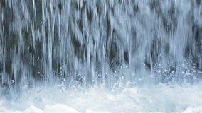 Agua de río que cae en una cascada entre los descensos y la espuma blanca almacen de video