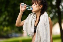 Agua de relajación y potable de la muchacha caucásica joven después de ejercitar Foto de archivo