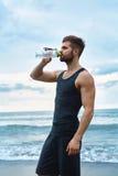 Agua de restauración de consumición del hombre después del entrenamiento en la playa bebida imágenes de archivo libres de regalías
