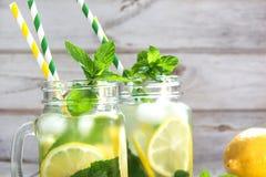 Agua de restauración del verano con el pepino, el limón, la menta y el hielo en tarro de albañil en un fondo de madera blanco rús Foto de archivo libre de regalías
