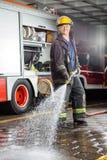 Agua de rociadura del bombero confiado durante práctica Imagen de archivo libre de regalías