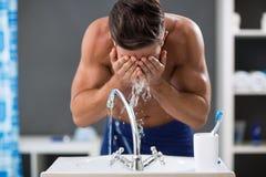 Agua de rociadura del hombre joven en su cara después de afeitar imagenes de archivo