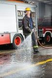 Agua de rociadura sonriente del bombero durante el entrenamiento Imagenes de archivo
