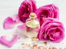 Agua de Rose en una botella con las flores y los pétalos de las rosas Fotos de archivo libres de regalías