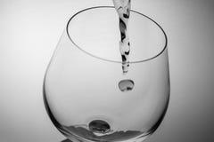 Agua del chapoteo en el vidrio del coñac Imagen de archivo libre de regalías