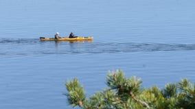 Agua del deportista con la paleta mientras que rema un kajak en el lago con el surfaceL del agua azul metrajes