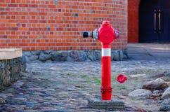 Agua del fuego rojo que viene una boca de riego de la calle cerca de una pared Imagen de archivo libre de regalías