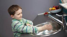 Agua del grifo de colada del muchacho en un vidrio Imagen de archivo libre de regalías