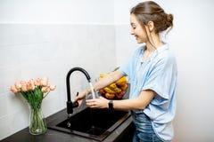 Agua del grifo de relleno de la mujer en la cocina imagen de archivo libre de regalías