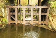Agua del pequeño flujo del río en el vertedero de madera histórico Fotos de archivo