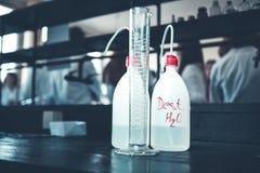 Agua desionizada purificada destilada en botellas plásticas con una bomba Cilindro graduado de medición para el volumen de medici Fotos de archivo libres de regalías