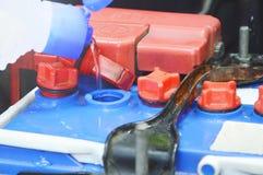 agua destilada que fluye de embotellado en baterías de coche imagen de archivo libre de regalías