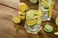 Agua dulce con el limón, la menta, el jengibre y el pepino en un de madera Foto de archivo